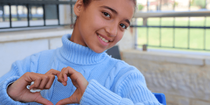 A girl wearing a pale blue jumper and hair pulled back in a bun is pictured with her thumbs and forefingers together in the shape of a heart.