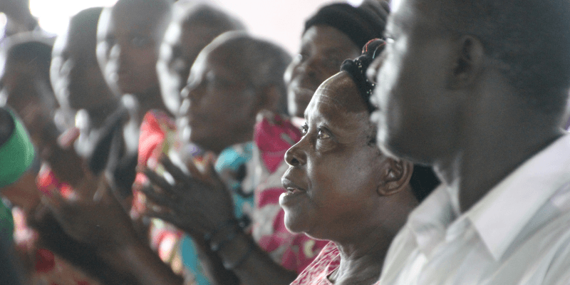 A group of worshippers stand in a pew in a church in Uganda. They are pictured in song, hands clapping to the music.