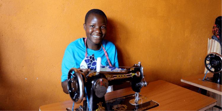 A girl smiles at her sewing machine in Uganda