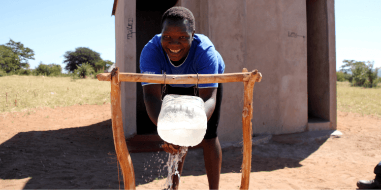 Glorious washes her hands in a tippy-tap in Zimbabwe