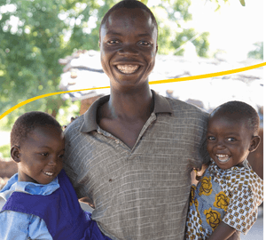 Man smiling with his young children