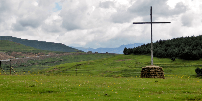 A wooden cross pictured in a mountainous landscape in Lesotho.