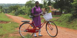 Nawalat stands by her bicycle in Uganda