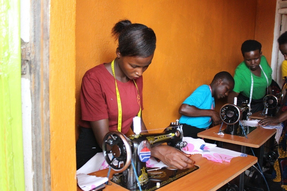 Young women receiving training in tailoring in COFCAWE's workshop