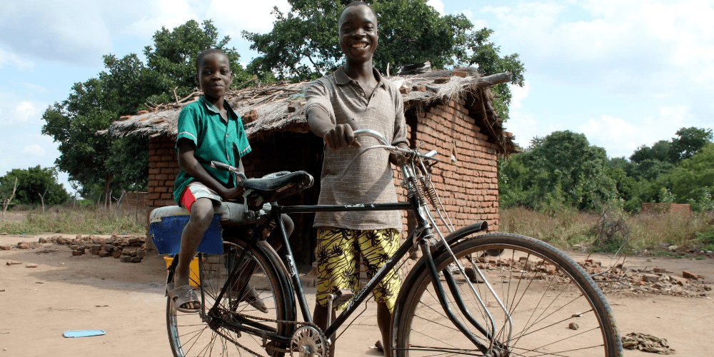 Shanu and his son smile alongside their bicycle