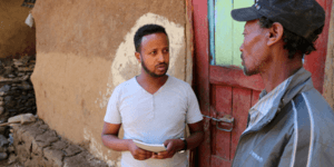 One of All We Can's local partner staff talks to a Village Chairman in Ethiopia, standing outside a homestead with a red and teal front door.