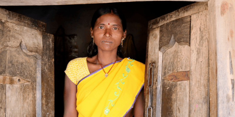 Khushboo stands in the doorway of her home