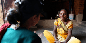 Manato, dressed in a yellow Sari, sits cross legged opposite an employee of one of All We Can's local partners in India