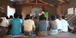 A teacher wearing a green jacket points to a blackboard in a classroom in Malawi. A group of girls watch attentively, their backs to the camera.