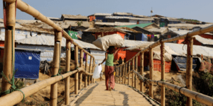 A child walks over a wooden bridge in a refugee camp in Cox's Bazar