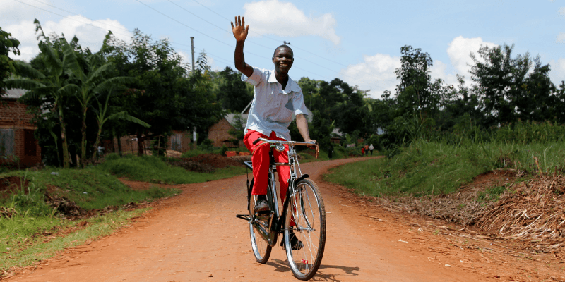 A teenage boy wearing red trousers and a blue shirt, waves whilst riding a bicycle.