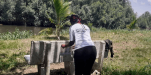 A woman attaches a Covid-19 awareness poster to a bench in Cameroon.