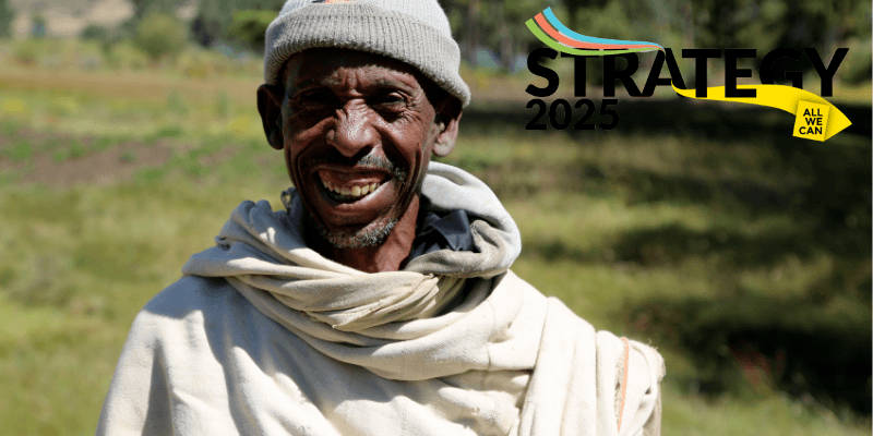 A farmer, dressed in white with a grey hat, stands in the land surrounding his home in Ethiopia. A logo in the corner reads 'Strategy 2025'