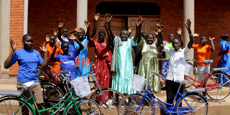 Parents and their children raise their arms in celebration outside a church in Uganda.
