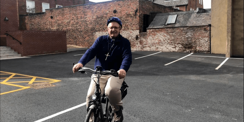 Revd Richard Teal, 2019/20 President of the Methodist Conference, takes part in a sponsored cycle event for All We Can. He wears beige trousers, a blue long sleeved jacket, a navy cycling helmet and is pictured in a car park.