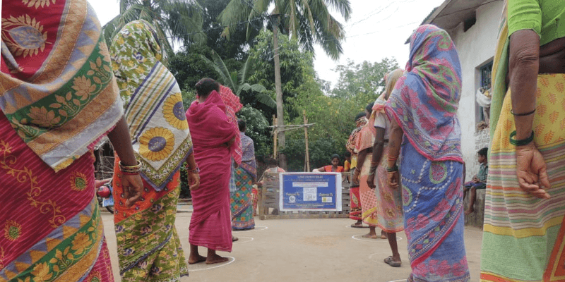 Women line up, socially distanced, to receive food and hygiene supplies during India's first Covid-19 wave.