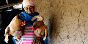 Fikerte, wearing a pink striped top, pink headscarf and blue wrap, holds two chickens outside her home in Ethiopia.