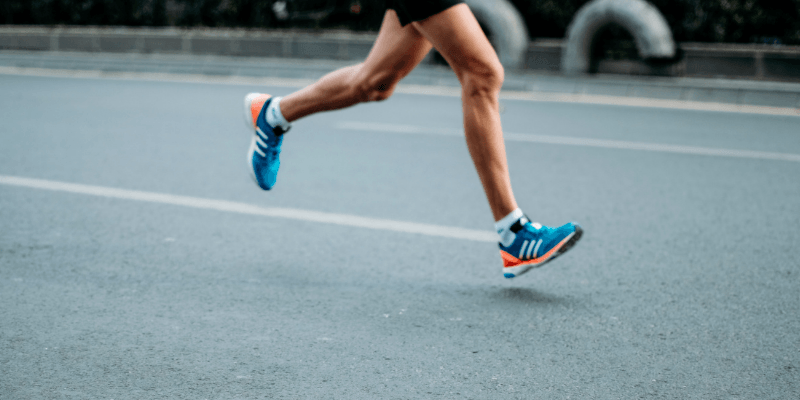 A runner wearing blue trainers