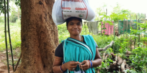 A woman in a blue sari smiles at the camera. Emergency food rations and sanitary equipment are in a bag balanced on her head. In the background is a tree and some washing.