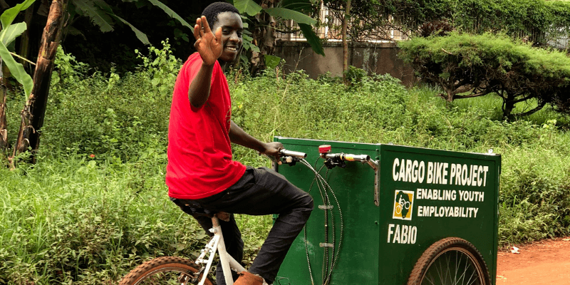 Bernard, in a red top and dark trousers, waves as he cycles on an adapted cargo bike.