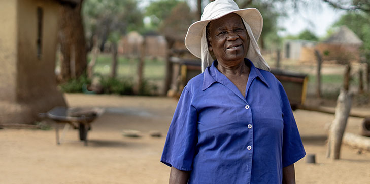 A woman stands in her yard, wearing a blue shirt and wide brimmed hat.